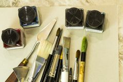Kunstwerkzeuge, Bürsten, acrylsauer auf einem grauen Album für das Zeichnen Stockfoto