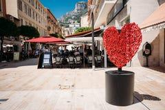 Kunstzusammensetzung von Bolzen und von rotem Herzen der Nüsse in Form auf Prinzessin Lizenzfreie Stockfotos