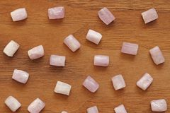 Kunzite jest naturalnym menchii kamieniem dla tworzyć biżuterię na naturalnym drewnianym tle Naturalni kryształy menchie i bzów k obraz royalty free