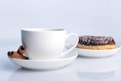 Kupa av kaffe med den söta munken Arkivbilder