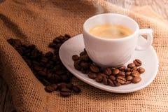 Kupa av kaffe med kaffebönor Arkivbild
