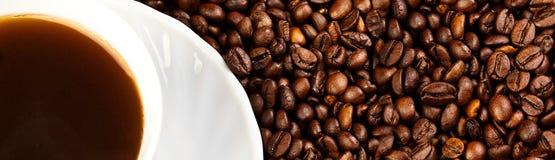 Kupa av kaffe med kaffebönor Arkivfoton