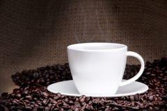 Kupa av kaffe med kaffebönor på en härlig bakgrund. Arkivbild