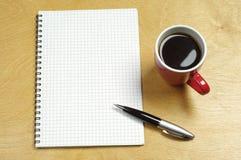 Kupa av kaffe och anteckningsbok Royaltyfri Bild