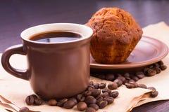 Kupa av kaffe och bönor med tårtan Royaltyfria Bilder