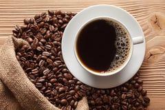 Kupa av kaffe och kaffebönor arkivbild