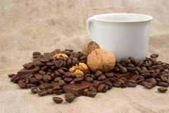 Kupa av kaffe, valnötter, kaffebönor och choklad royaltyfria bilder