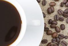 Kupa av svart kaffe med bönor på hessian arkivfoton