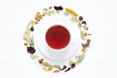 Kupa av Tea Örtte, torra örter och blommor med stycken av frukt och bär arkivfoto