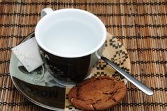 Kupa av tea och en kaka arkivfoton