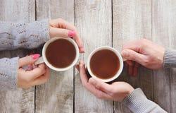 Kupa av tea räcker in Royaltyfria Foton