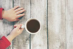 Kupa av tea räcker in Royaltyfria Bilder