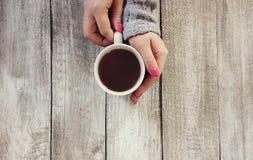Kupa av tea räcker in Arkivbild