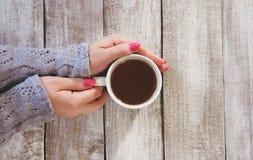 Kupa av tea räcker in Arkivfoton