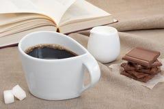 Kupa kaffe på linneborddukar med stycken av choklad, socker Royaltyfri Foto