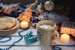 Kupa kakao med marshmallowen, den hemlagade chokladkakan och jordnötkexet som tänds stearinljus, xmas-trädgarnering på träbackgro royaltyfria foton