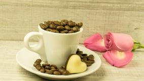 Kupa mycket av kaffebönor av en ros royaltyfria foton