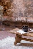 Kupa och boka på trästol på ljus matta i minsta och industriell plan inre med växten arkivbilder