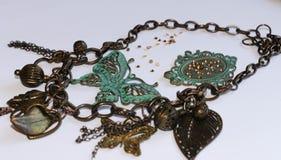 Kupferne Kette mit dekorativen grünen Schmetterlingen, Blättern, Blumen, Herzen und Perlen auf Grau stockbilder