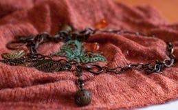 Kupferne Kette mit Schmetterlingen, Perlen, dekorative Blätter auf strukturiertem Terrakottastoff lizenzfreie stockfotos