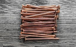 Kupferne Nägel auf hölzernem Brett Stockfotos