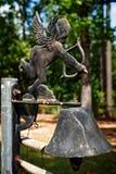 Kupidon och en Klocka i en kyrkogård Royaltyfri Fotografi