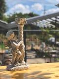 Kupidonskulpturkonst på trätabellen med naturligt solljus royaltyfri foto