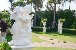 Kupidonstaty i trädgård Royaltyfria Foton