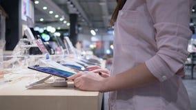 Kupienie elektronika, żeńska nabywca bada opóźnionego nowożytnego pastylka komputer i przegląda je w rękach w sklepie zbiory