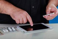Kupienie medycyna nad internetem, męskie ręki trzyma pigułki narkotyzuje próbkę i pisać na maszynie rozkaz na laptop klawiaturze obrazy stock