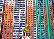 Kupol av den lilla kyrkan mot den stora moderna byggnaden Royaltyfri Bild