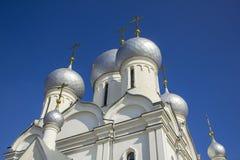 Kupoler av en vit ortodox kyrka med guld- kors mot den blåa klara himlen, nedersta sikt arkivbild