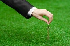 Kupować nowego domu, ziemi lub biznesu temat: wręcza w czarnym kostiumu trzyma klucz nowy dom na tle zieleni gras Zdjęcie Stock