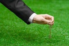 Kupować nowego domu, ziemi lub biznesu temat: wręcza w czarnym kostiumu trzyma klucz nowy dom na tle zieleni gras Zdjęcie Royalty Free