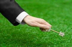 Kupować nowego domu, ziemi lub biznesu temat: wręcza w czarnym kostiumu trzyma klucz nowy dom na tle zieleni gras Obrazy Stock