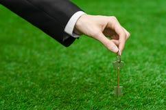 Kupować nowego domu, ziemi lub biznesu temat: wręcza w czarnym kostiumu trzyma klucz nowy dom na tle zieleni gras Obraz Stock