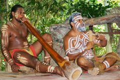 Aborigine actors perform music with traditional instruments in the Tjapukai Culture Park in Kuranda, Queensland, Australia. stock images