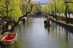 KURASHIKI, JAPAN - 31. M?RZ 2019: Touristen genie?en das altmodische Boot entlang dem Kurashiki-Kanal lizenzfreie stockfotos