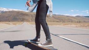 KURAY RÚSSIA - 01 05 2017: mulher que skateboarding rapidamente na estrada Mulher que faz o longboard para baixo e que monta o se filme