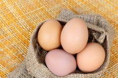Kurczaków brown jajka w workowej torbie nad bambusem wyplatają tło obraz royalty free