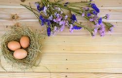 Kurczaków jajka w gniazdeczku z drewnianym tłem Obrazy Stock