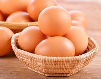 Kurczaków jajka w koszu na popielatym drewnianym tle Zdjęcia Stock