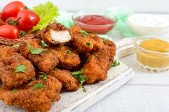 Kurczak bryłki Kawałki smażący crispy mięso na papierze z różnymi kumberlandami, fotografia stock