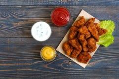 Kurczak bryłki Kawałki smażący crispy mięso na papierze z różnymi kumberlandami na drewnianym stole, obrazy royalty free
