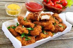 Kurczak bryłki Kawałki smażący crispy mięso z różnymi kumberlandami na drewnianym stole, zdjęcie royalty free