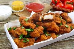 Kurczak bryłki Kawałki smażący crispy mięso z różnymi kumberlandami na drewnianym stole, zdjęcia stock