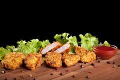 Kurczak bryłki na drewnianym stole z kumberlandem i sałatą, Zdjęcie Stock