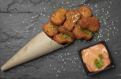 Kurczak bryłki z sezamowymi ziarnami i kumberlandem na czarnego talerza odgórnym strzale zdjęcie royalty free
