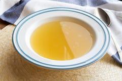 Kurczak kości rosół słuzyć w białym i błękitnym talerzu Zdjęcie Stock
