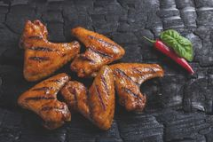 Kurczaka skrzydło piec na grillu smażył czarnego tło węgiel drzewny barbecue grilla odizolowywającego Obraz Stock